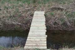 Flot, flot bro over åen der tilsyneladende løber den forkerte vej